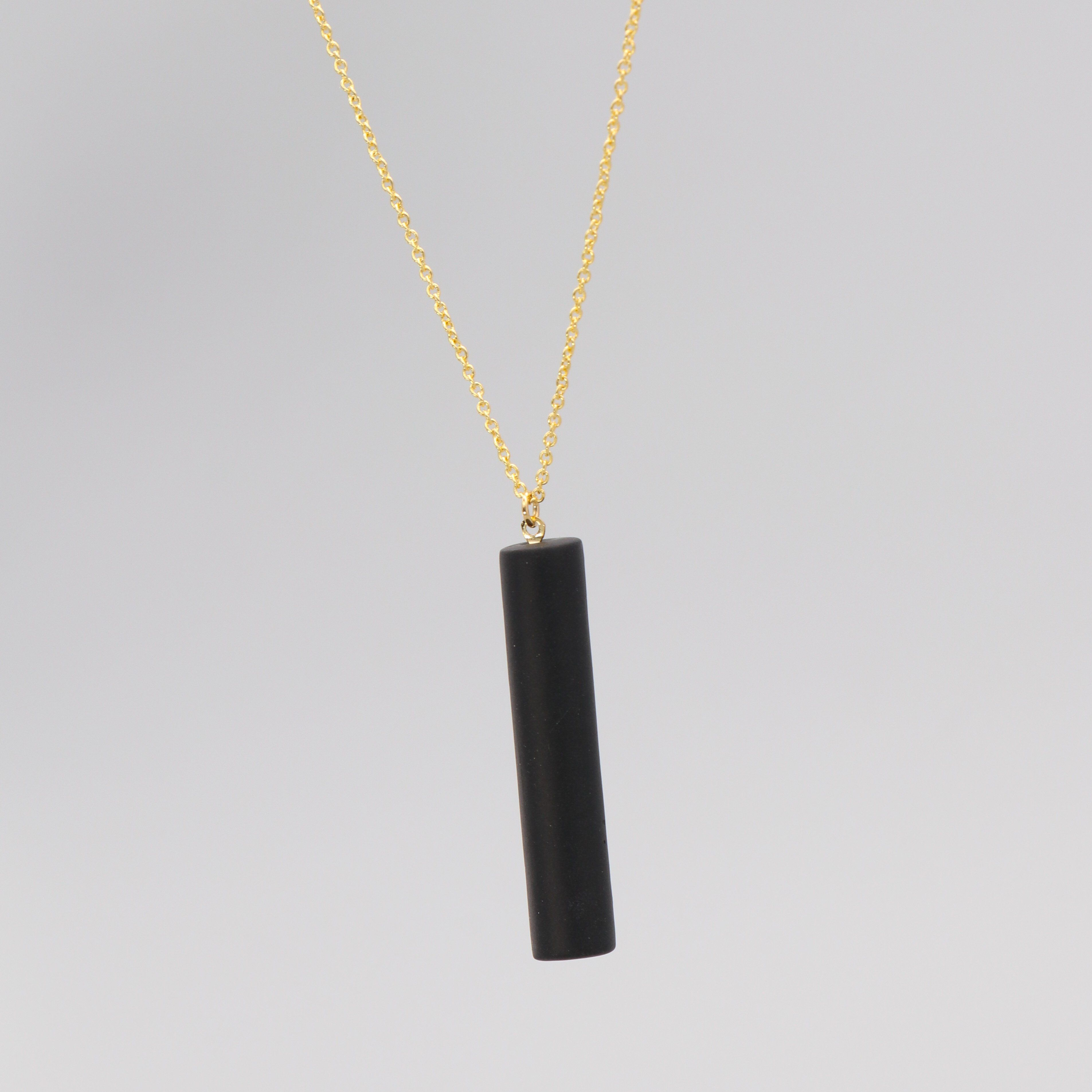 Gold necklace with a black bar pendant